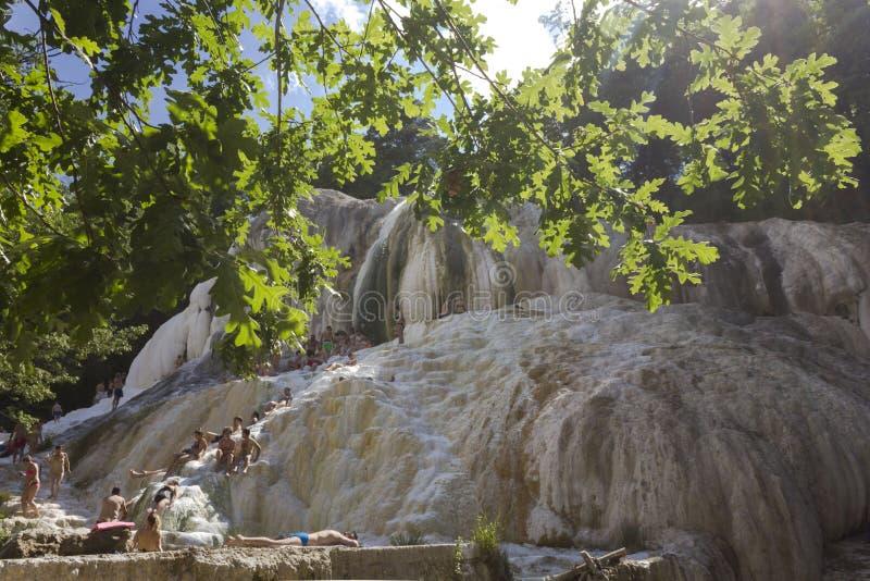 Les gens se baignant en courant ascendant naturel de Bagni San Filippo photo stock
