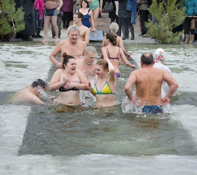 Les gens se baignent en rivière en hiver. Épiphanie chrétienne de festival religieux image stock