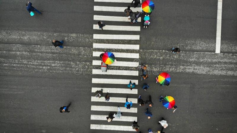 Les gens se serrent croisant un passage pi?ton pi?tonnier dans un jour m?chant Certains d'entre eux avec le parapluie color? Vue  photo stock