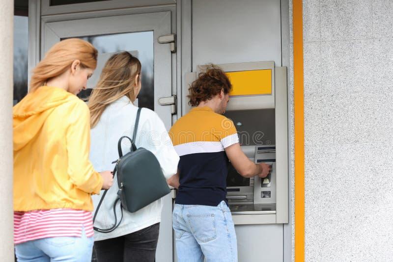 Les gens se tenant dans la file d'attente au distributeur automatique de billets photos stock