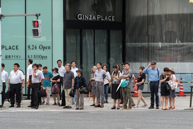 Les gens se tenant sur le signal rouge du feu de signalisation à la rue dans la banlieue de Ginza, Tokyo photographie stock libre de droits