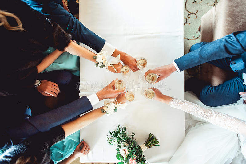 Les gens se tiennent en verres de mains avec du vin blanc Un bon nombre de verres de vin sur la table verte photos stock