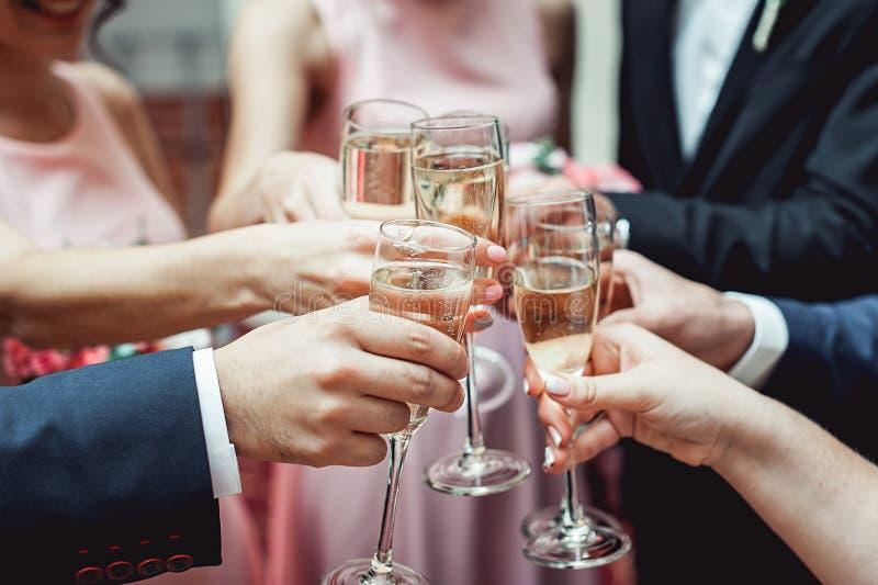 Les gens se tiennent en verres de mains avec du vin blanc Un bon nombre de verres de vin sur la table verte photographie stock