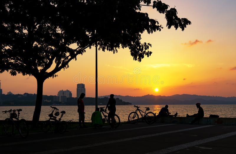 Les gens silhouettent avec la bicyclette pendant le coucher du soleil photographie stock