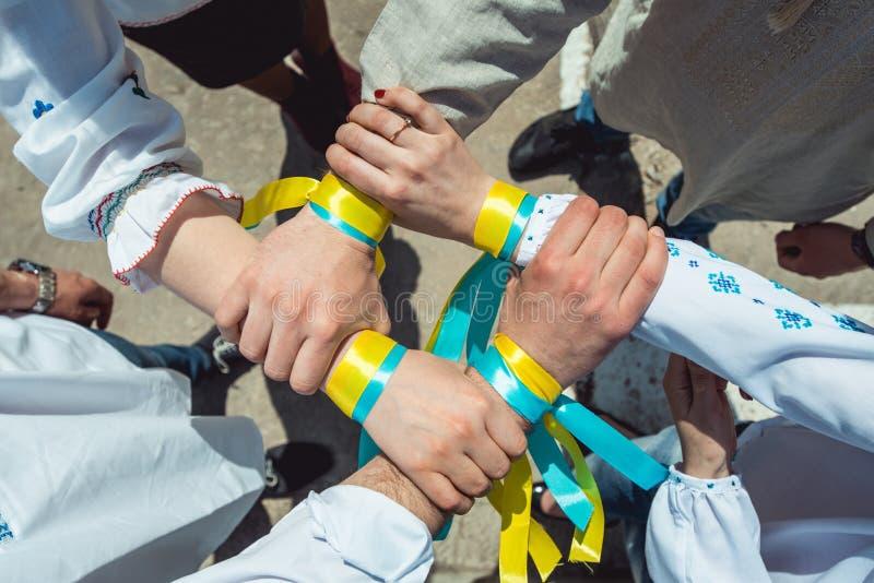 Les gens sont habillés dans des vêtements ukrainiens traditionnels tenant leurs mains ensemble, unification de succès de la natio image libre de droits