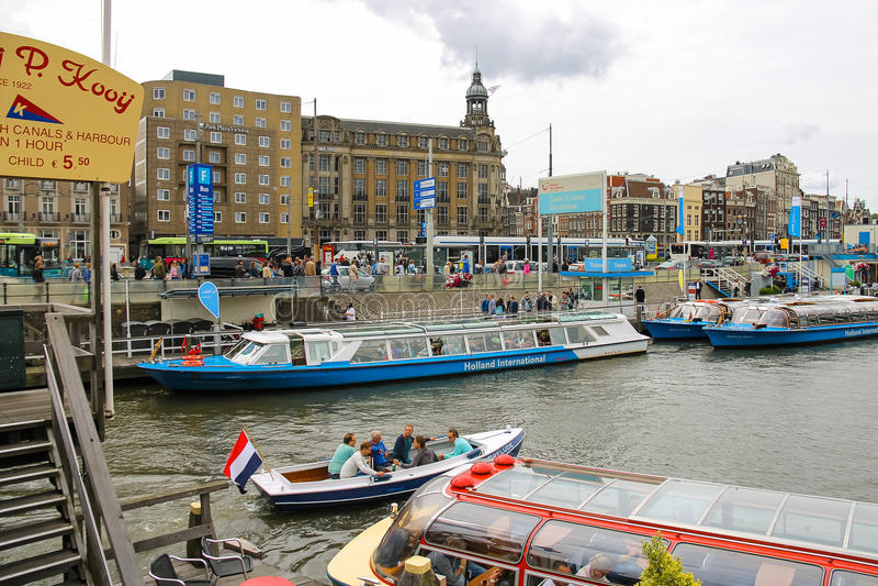Les gens sur l'atterrissage de dock sur des bateaux de croisière de rivière, Amsterdam images stock