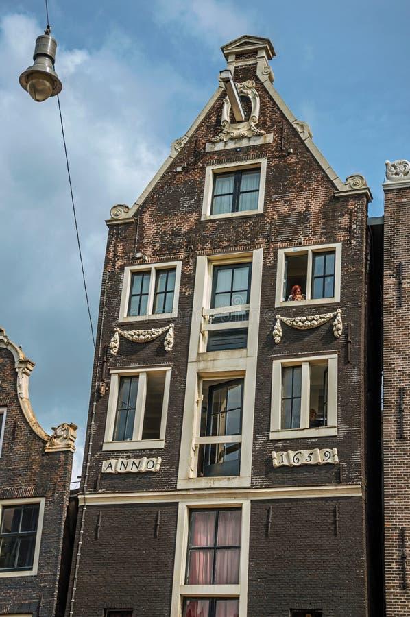 Les gens sur la fenêtre du vieil immeuble de brique avec le ciel bleu ensoleillé à Amsterdam image stock