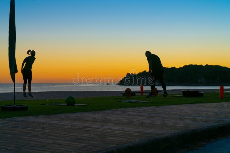 Les gens sur la plage au bâti Maunganui au lever de soleil en silhouette faisant l'exercice de fitnes de matin et marchant par photographie stock