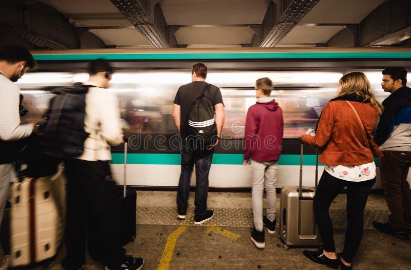 Les gens sur le platfor avec passer rapidement le train de départ photographie stock