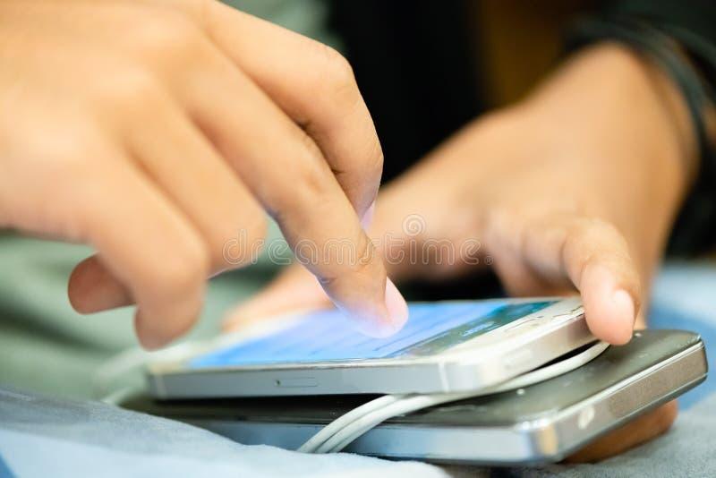 les gens surfant et passant en revue le Web au t?l?phone intelligent les gens appr?cient avec le jeu dans le r?seau social de m?d photos libres de droits