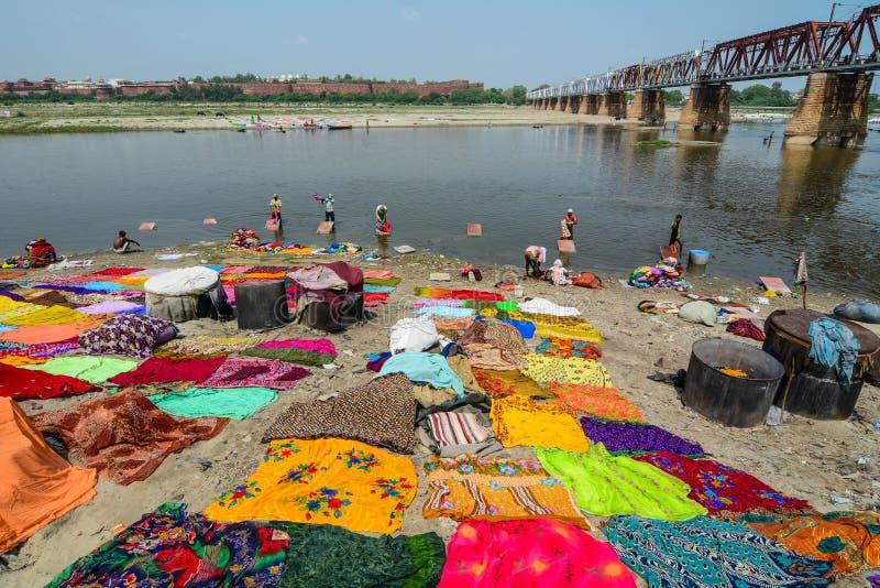 Les gens teignent les vêtements traditionnels sur la rive photo stock