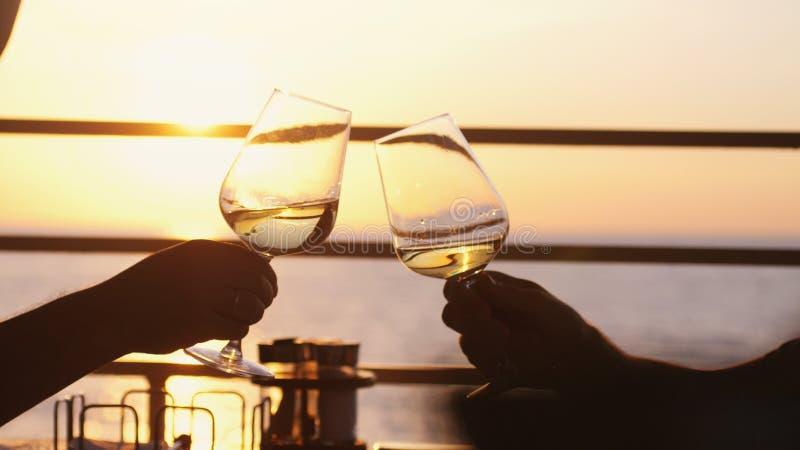 Les gens tenant le verre de vin, faisant un pain grillé au-dessus de coucher du soleil Amis buvant du vin blanc, grillant taule P photographie stock