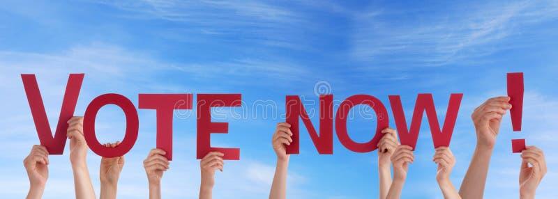 Les gens tenant le vote maintenant dans le ciel photo stock