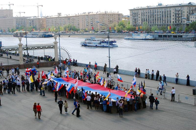 Les gens tiennent un drapeau russe et se tiennent prêt la rivière de Moscou. image stock