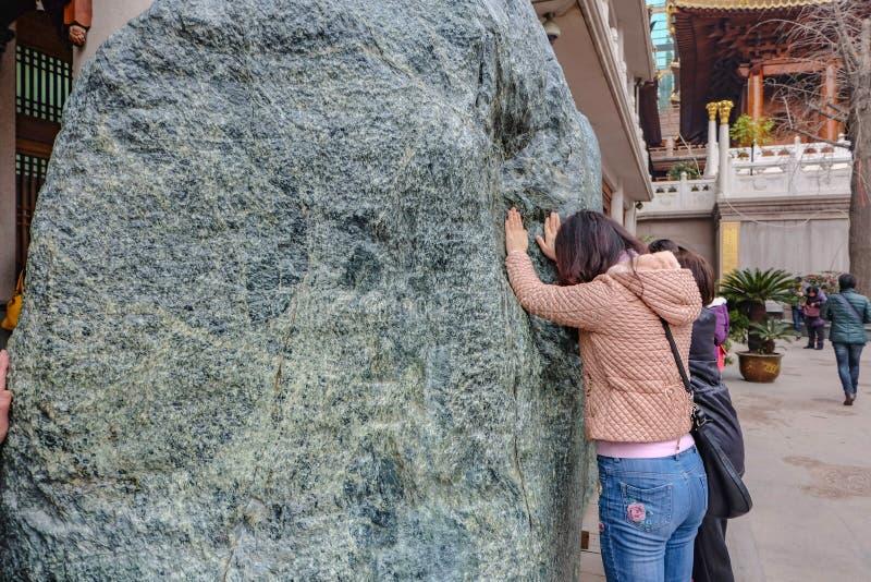 Les gens touchent la grande pierre d'esprit dans jian une porcelaine de ville de Changhaï de temple images libres de droits