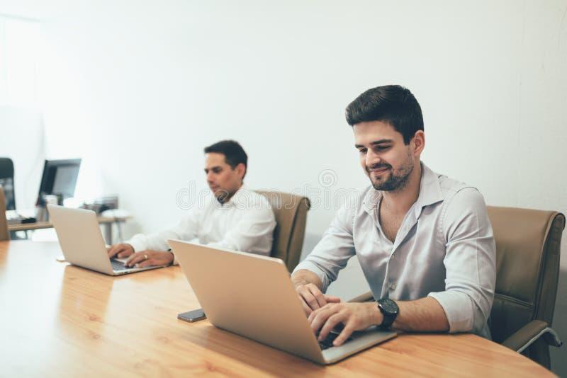 Les gens travaillant sur des ordinateurs portables dans le bureau photo stock