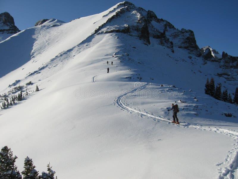 Les gens trimardant par la neige à la crête de montagne image stock
