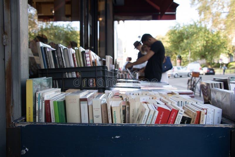 Les gens vérifiant les livres français utilisés à une librairie extérieure de support à Paris central photographie stock
