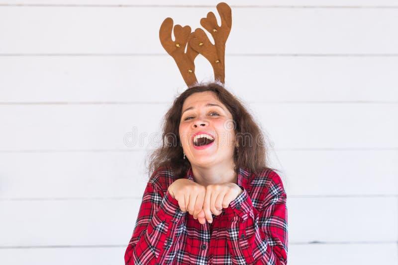 Les gens, les vacances et le concept de Noël - fille drôle de Santa dans des klaxons de cerfs communs sur sa tête sur le fond bla images stock