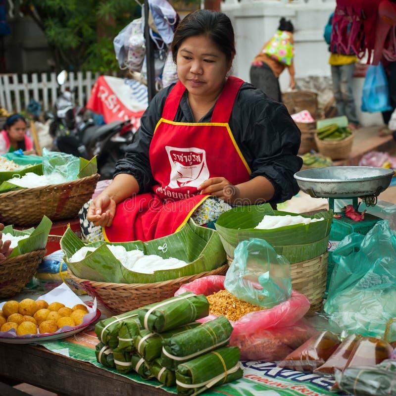 Les gens vendant la nourriture au marché asiatique traditionnel laos image stock