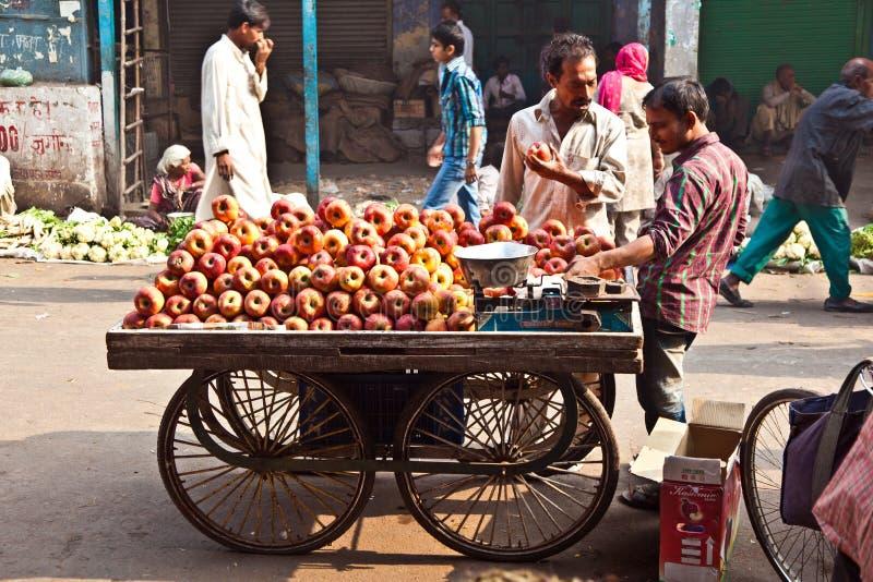 Les gens vendent des pommes au Bazar de Chawri à Delhi, Inde image libre de droits