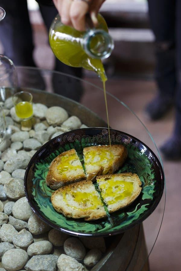 Les gens versant l'huile d'olive vierge supplémentaire sur des tranches de pain photographie stock libre de droits