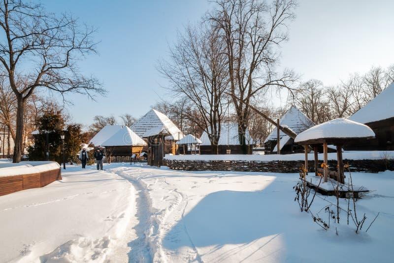 Les gens visitant le village roumain traditionnel en hiver images libres de droits