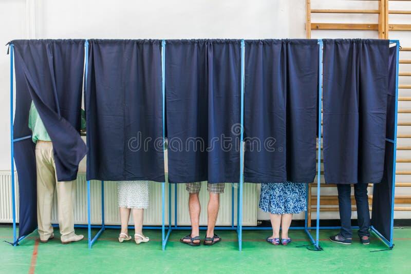 Les gens votant dans les cabines images stock