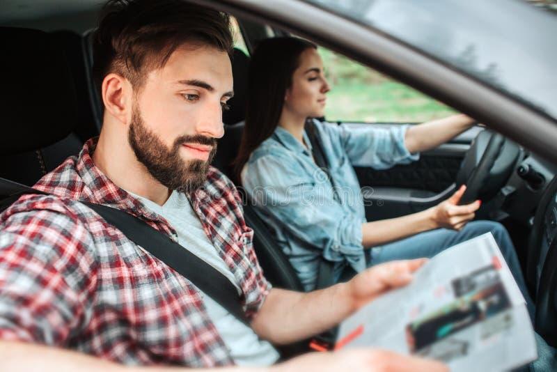 Les gentilles personnes montent dans la voiture La fille conduit la machine Le type s'assied sans compter que la sa et lit un liv photos stock