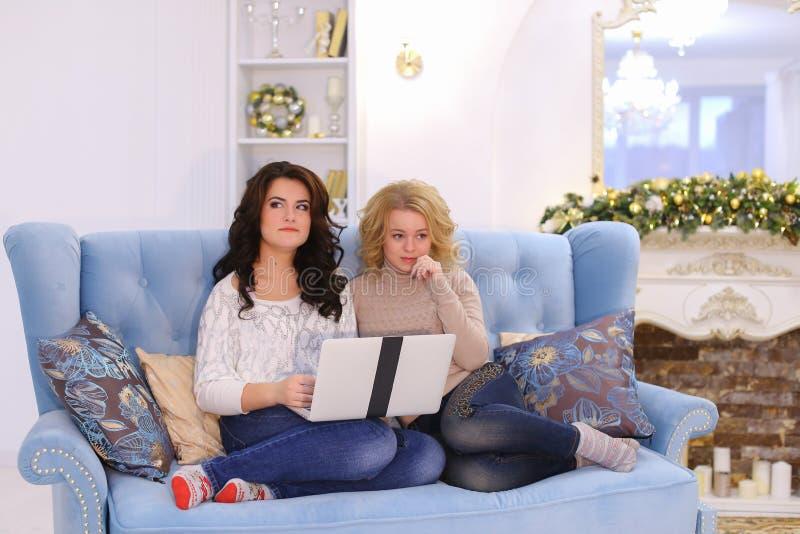 Les gentils amis drôles passent la soirée agréable à l'ordinateur, la séance o photos stock