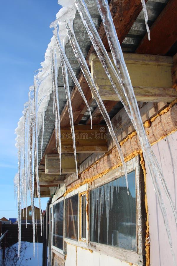 Les glaçons de fonte de ressort accrochent du toit la maison en mars photographie stock