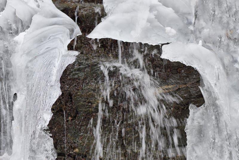 Les glaçons de glace accrochent sur des roches de montagne dans un jour d'hiver froid avec le wat photographie stock libre de droits