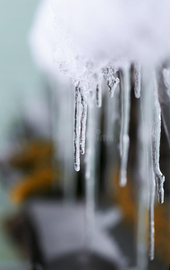 Les glaçons pendent du vieux dégel de toit au printemps images stock