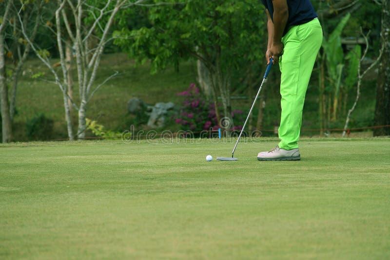 Les golfeurs brouillés tapotent le golf dans le terrain de golf de soirée dans T image libre de droits