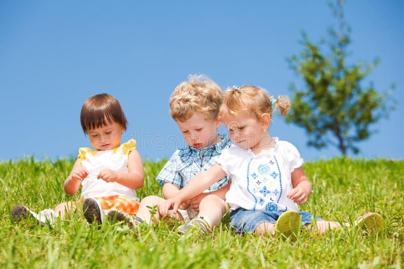 Les gosses s'asseyent sur l'herbe photo libre de droits