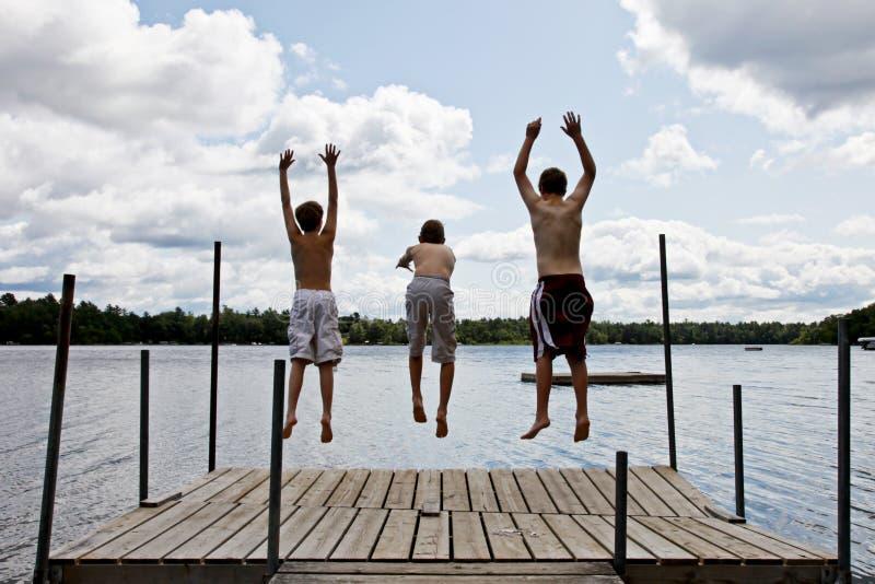 Les gosses sautant dans le lac image libre de droits
