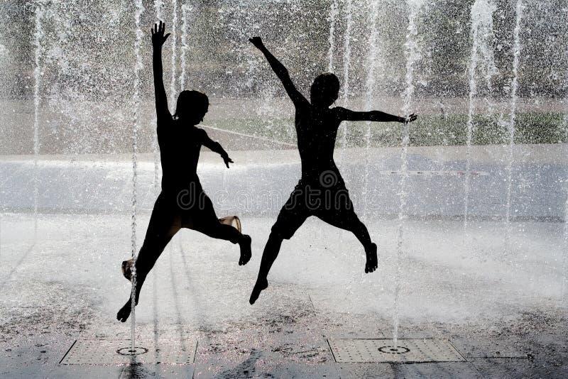 Les gosses sautant le jeu dans la fontaine image stock