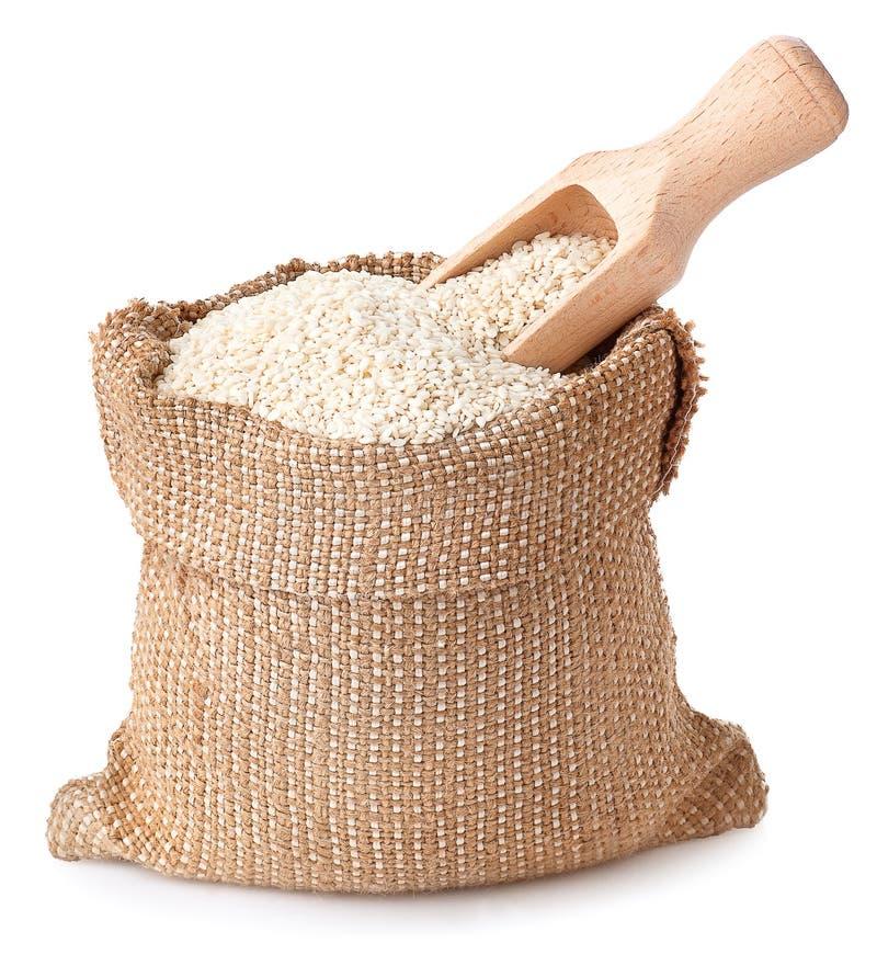 Les graines de sésame avec le scoop en bois en plan rapproché de sac photos stock
