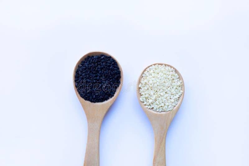 Les graines de sésame noires et blanches sur la cuillère en bois, fond blanc image stock