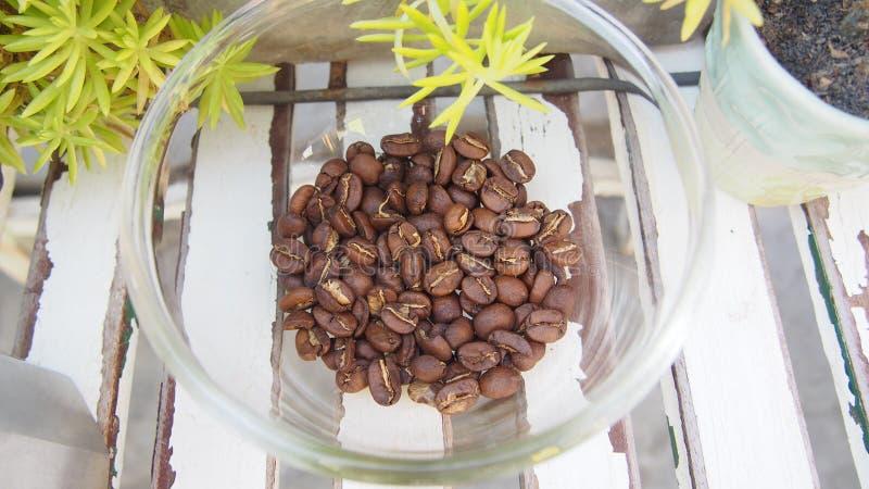 Les grains de café amassent dans le tas en verre sur la table en bois, vue supérieure image libre de droits