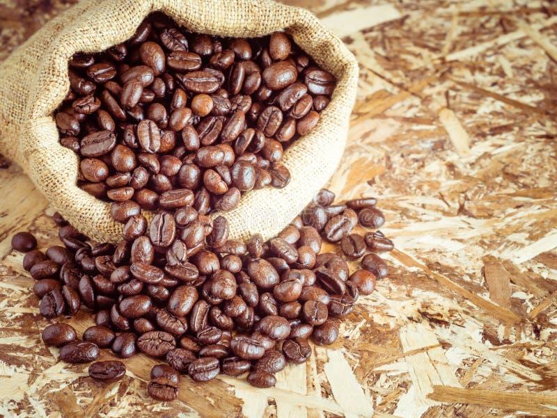 Les grains de café dans un sac avec le filtre effectuent rétro photo libre de droits