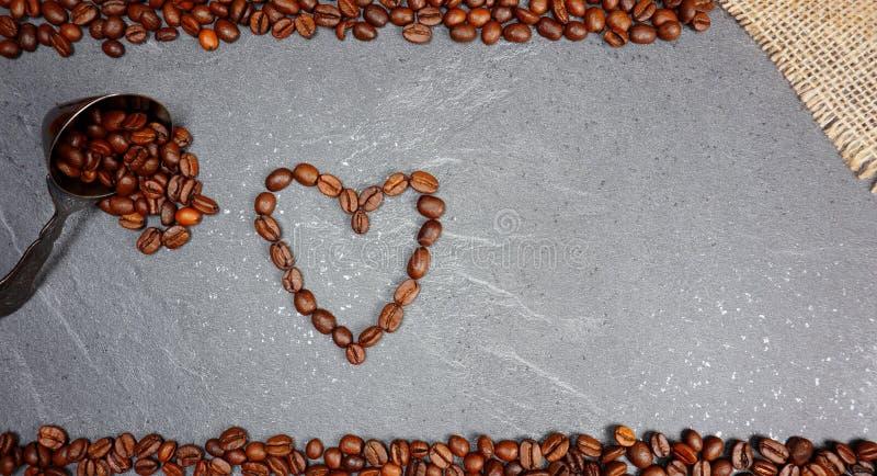 Les grains de café desserrent le commerce équitable avec la cuillère et le coeur au fond de plan de travail de cuisine image stock