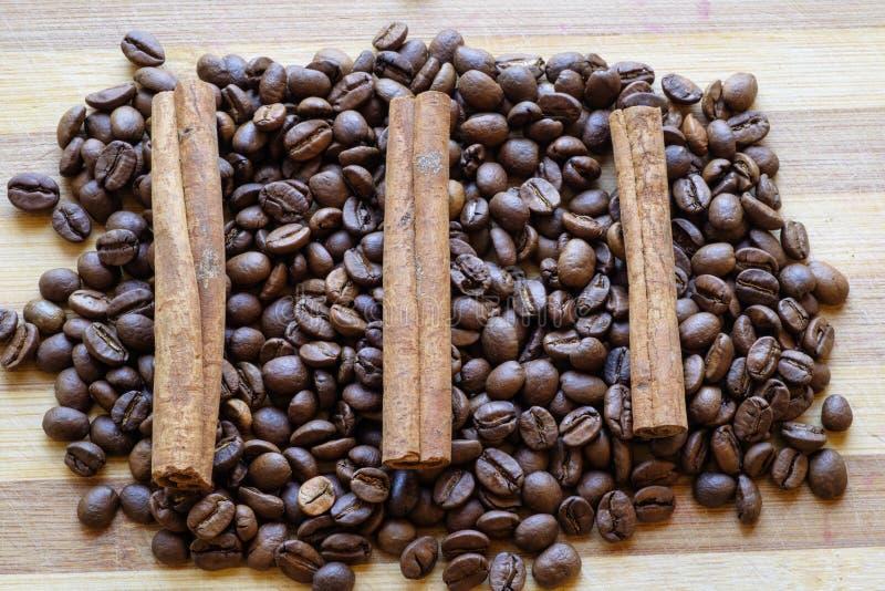 Les grains de café et les bâtons de cannelle ajustent le dessus de paysage photographie stock libre de droits