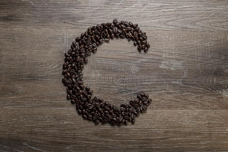 Les grains de café ont arrangé comme lettre C images stock