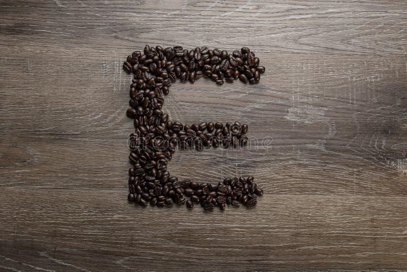 Les grains de café ont arrangé comme lettre E photographie stock libre de droits