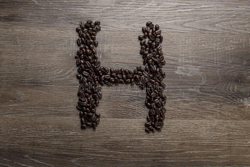 Les grains de café ont arrangé comme lettre H image stock