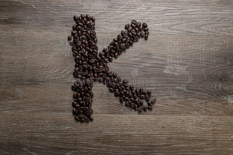 Les grains de café ont arrangé comme lettre K images stock