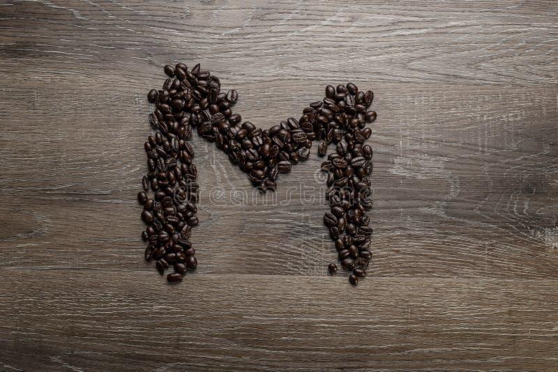 Les grains de café ont arrangé comme lettre M photo libre de droits