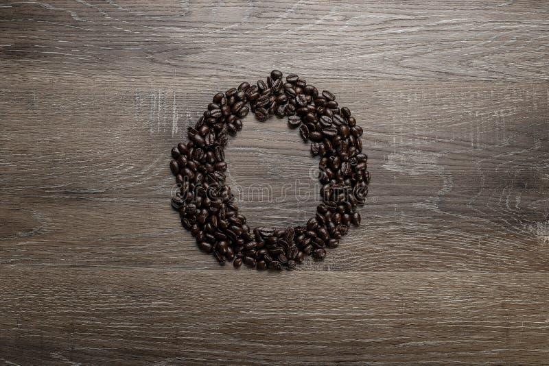 Les grains de café ont arrangé comme lettre O images stock