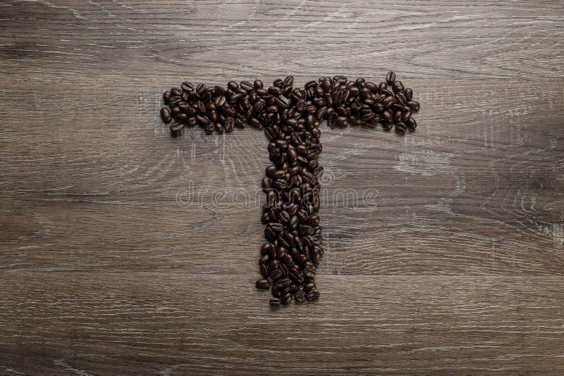 Les grains de café ont arrangé comme lettre T images libres de droits